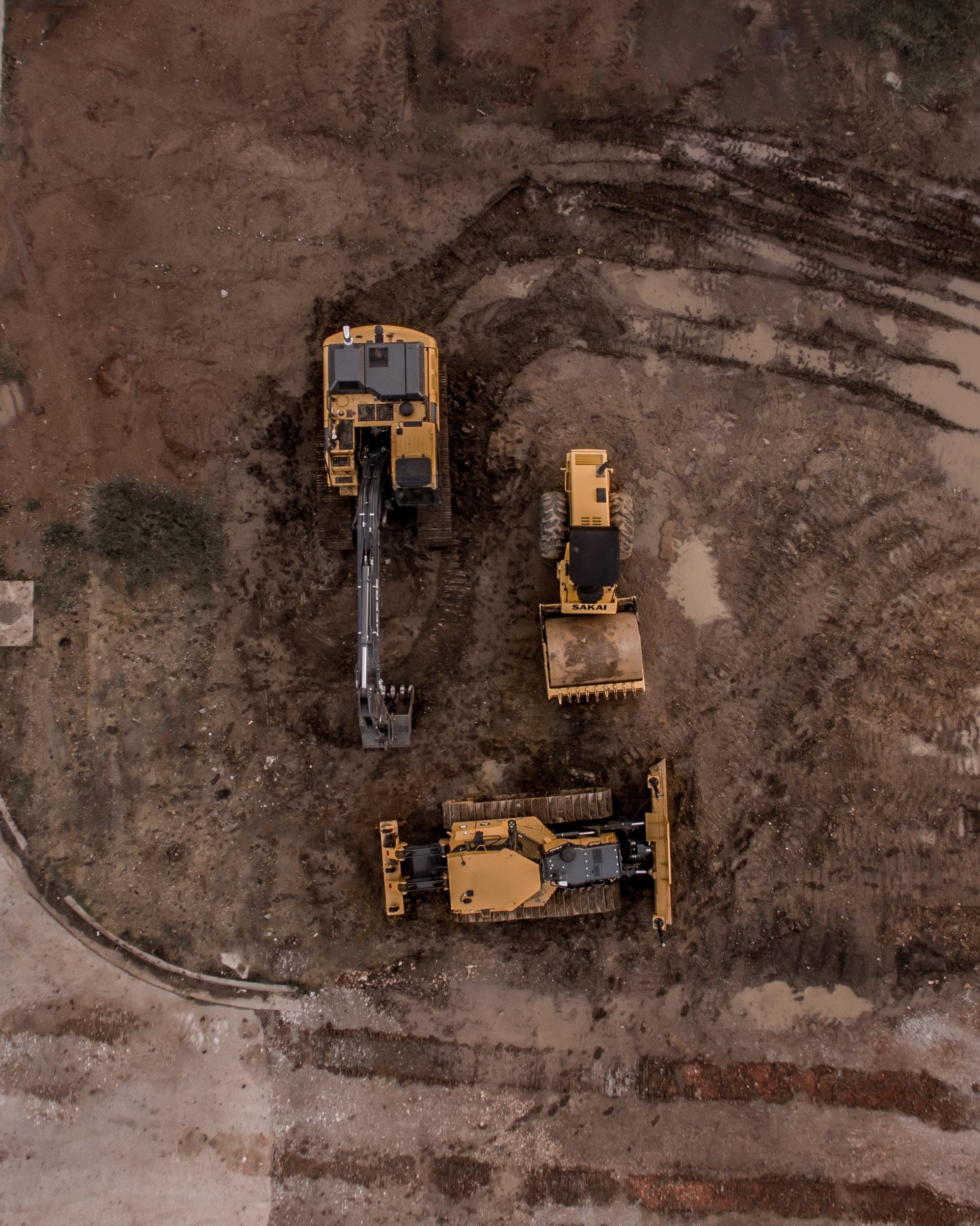 aerial-photo-of-excavator-road-roller-and-bulldozer-1579356